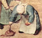 Nena remenant caca amb un pal